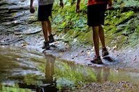 Two hikers walk next to a creek. (FILE)