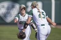 Taylor Saxton, left, and Mikayla Cooper high-five after an out during Ohio's game against Buffalo on Friday. The Bobcats beat the Bulls 9-1.