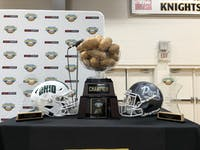 Ohio and Nevada's helmets pose with the Famous Idaho Potato Bowl trophy at Bishop Kelly High School on Monday, Dec. 30, 2019.