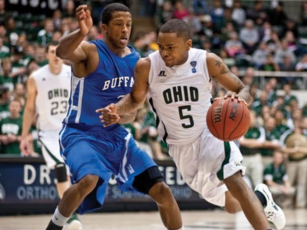 Ohio's D.J. Cooper dribbles by a Buffalo player as he drives down the court. The Bobcats defeated the Bulls 60-52 on Jan. 12, 2012. (FILE)