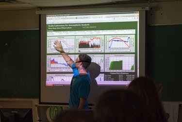 OU graduate student Kyle Clem explains data collected at the West State Street Weather Station to Nelsonville-York fifth grade students during a visit to the Scalia Laboratory for Atmospheric Analysis at the Athens Campus. (Photo provided by Ben Siegel/Ohio University).