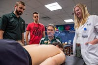 (Left to right) head athletic trainer for OU hockey Chayse Casto, Thai massage therapist Logan Black, Dr. Daniel Black and osteopathic medical student Kaitlin VanHooser watch over acupuncter applied to OU hockey forward Zach Curry in the Grover Athletic Training Lab on Wednesday, March 4, 2020.