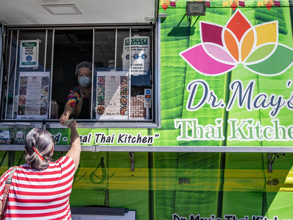 Belinda Fleming pays for her lunch order at Dr. May's Thai Kitchen food truck at the Athens Farmers Market on Saturday, Sept. 5, 2020. Dr. Mathurada Rath's lime green mobile restaurant is hard to miss among the tents set up on State Street every Saturday.