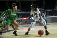 Ohio's guard Erica Johnson (No. 4) dribbles the ball while Marshall's forward Taylor Pearson (No. 20) defends on Nov. 13, 2019. (FILE)