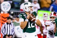 Ohio's quarterback Nathan Rourke (12) readies himself to throw the ball in a play against Miami during the 150th anniversary of college football held at Peden Stadium on Wednesday, Nov. 6, 2019.