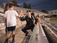 Cadet Isaac Culbert, a member of the color guard, high fives Chase Burnett (left) before the 2018 9/11 Stair Challenge at Peden Stadium. (FILE)