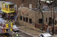 Firefighters view the damage of an explosion in the 100 block of West Union Street on Sunday evening.