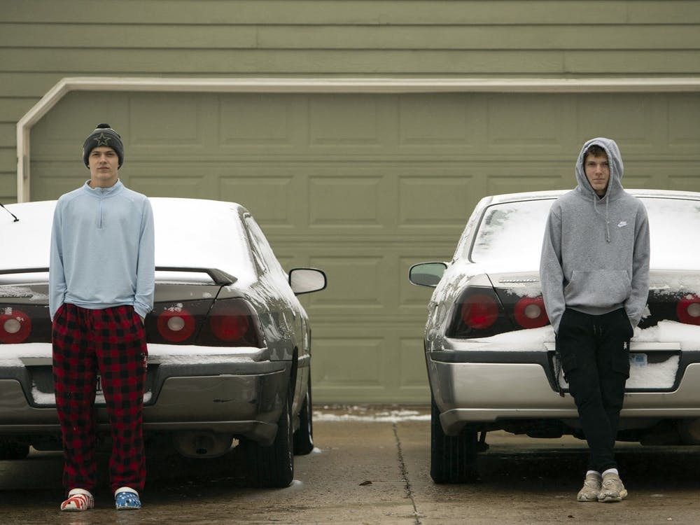 """Dallas, left, and Dominic, right, stand in front of their nearly identical cars, a 2005 and 2003 Chevy Impala, respectively, on Oct. 26, 2020, at their Mom's home in Lawrence, Kansas. Both cars were passed down to them from their maternal grandfather. Dominic has named his car Trinity and says, """"She is perfect."""" On the other hand, Dallas says, """"Why would I name my car?"""""""