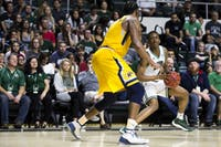 Ohio guard Teyvion Kirk (#4) eyes the basket above Kent State's Adonis De La Rosa (#1) during the Bobcats' 88-76 win in The Convo on Tuesday, Feb. 20.