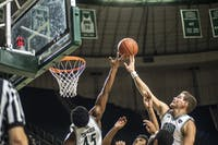Senior, Doug Taylor (#45), and freshman, Ben Vander Plas (#5), go up for the rebound during the bobcat's home game against Iona College on November 27.