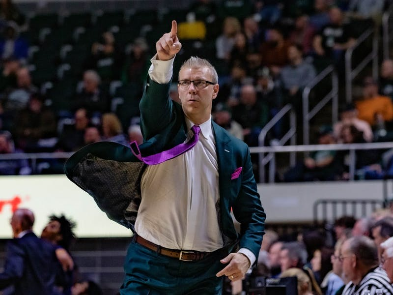 Head Coach Jeff Boals points to the score board while following the Bobcats in their match against Akron at the Convo on Saturday, Jan. 25, 2020.