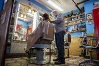Dave Smart, owner of Smart's Barbershop in Athens, Ohio, works on a hair cut for Ohio University student, Jack, on August 27, 2020.