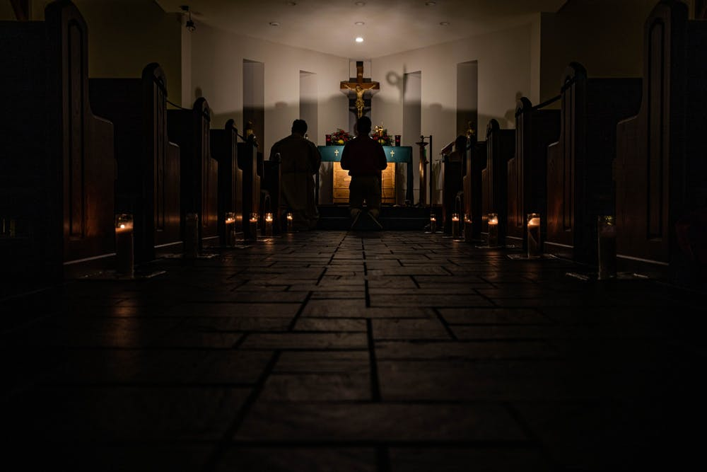 Students kneel before the cross, starting off the Eucharistic Adoration in Christ the King University Parish Catholic Church in Athens, Ohio, on Wednesday, Sept. 16, 2020
