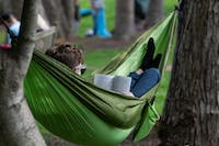 Ohio University senior Morgan Beard reads while in his hammock in Emeriti Park on Wednesday, April 17, 2019.