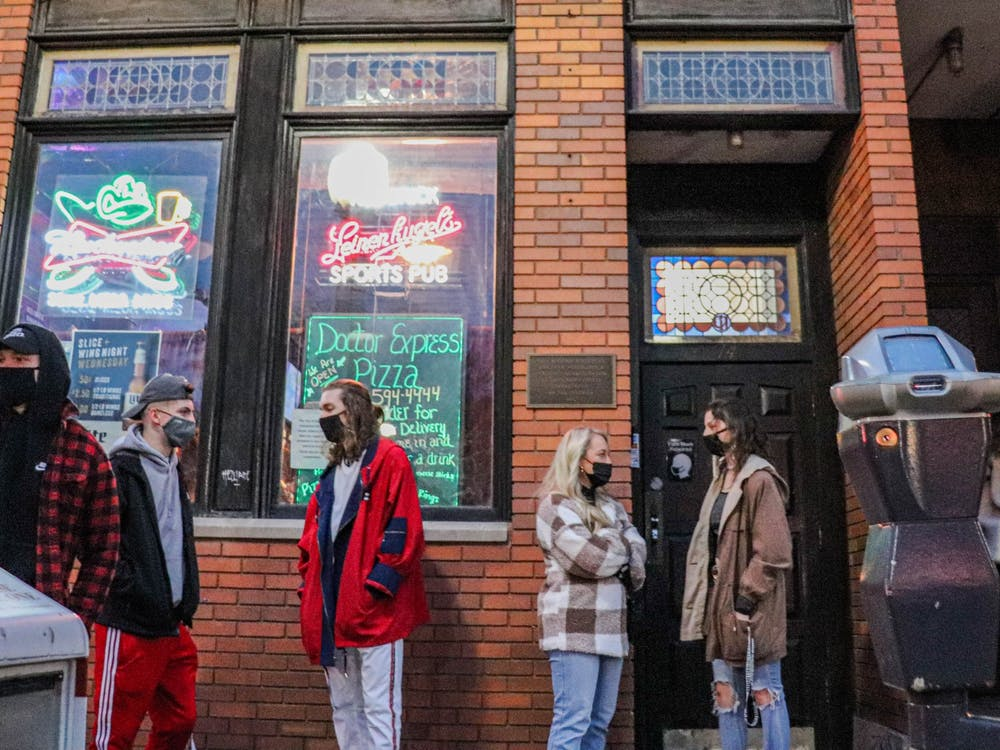 Masked individuals form a line outside Red Brick Tavern in Athens, Ohio, on Wednesday, Jan. 27, 2021. (FILE)