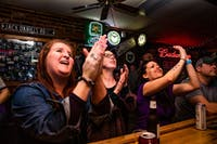 (Left to right) Heather Withee, Erin Tommas and Lauren Nichols react at Cat's Eye Saloon to an LSU's touchdown at the College Football Playoff National Championship against Clemson on Monday, Jan. 13. LSU quarterback Joe Burrow is a fan favorite in Athens for is heartfelt speech addressed to his Appalachian hometown and helped raise money for the local food bank. The Tigers champion over Clemson with a final score of 42-25.