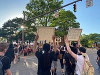 Protestors hold up signs while chanting and marching.