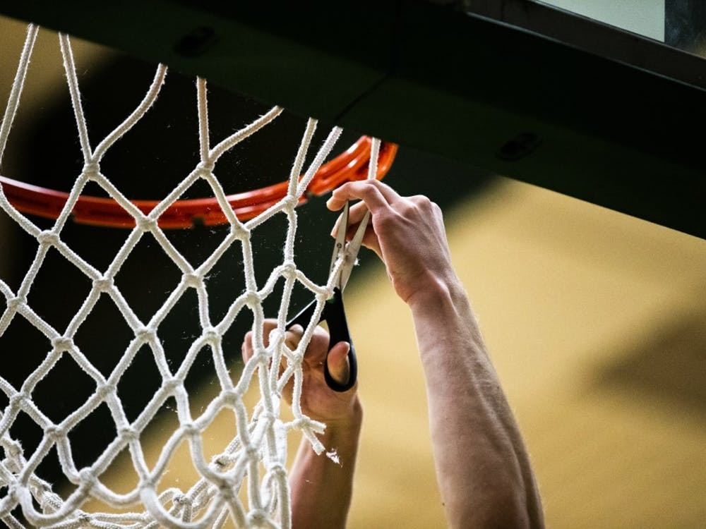 Athens guard Andre Stephens cuts down  a piece of the net after the Bulldogs clinched the TVC Conference title on Friday by defeating Meigs 55-51.