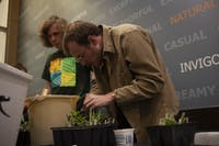 Sam Smith helps transplant cacti and other suculants into recycled containers for the growing line of students in Nelson Commons on Tuesday, Nov. 19, 2019.