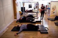 Kate Blyth of Athens (right) instructs a pilates class at Pilates of Athens on Thursday. Blyth's favorite part of instructing is helping people improve their body awareness.