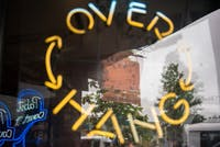 The Over Hang's sign reflected in the bar's window on Monday.