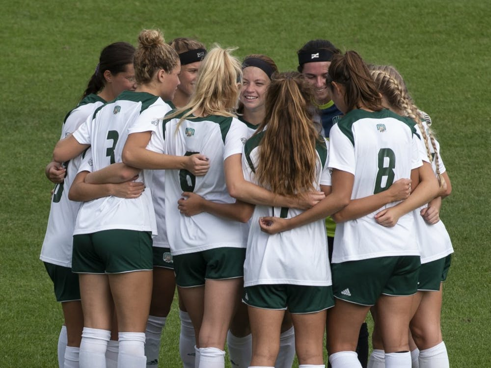 The women's soccer team huddles together before their game against the Akron Zips on Oct. 4, 2018.