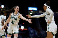 Ohio's Gabby Burris (left, #41) high-fives Cece Hooks during the MAC Championship Game on Saturday. (photo via Maddie Schroeder/Ohio Athletics)