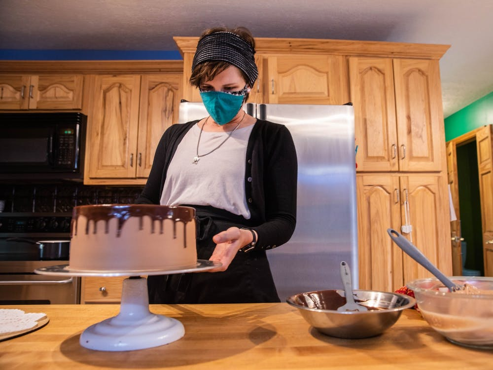 Megan McStevens, owner of Pinkterton's Cake Bakery, assembles the finishing touches on her Swiss meringue buttercream chocolate cake in her Nelsonville, Ohio, home for a customer on the morning of Thursday, Nov. 12, 2020.
