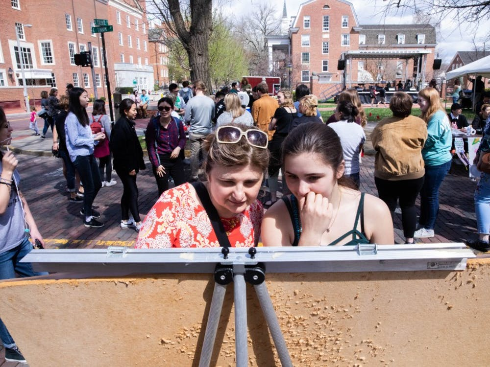 Ohio University student Anna Leatherwood (right) and her mom Svitlana Kalinichenko study a cultural origins map at the 50th Annual International Street Fair on Saturday.