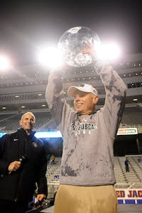 Ohio coach Frank Solich hoists the 2011 Famous Idaho Potato Bowl trophy after his team defeated Utah State, 24-23, at Albertsons Stadium.
