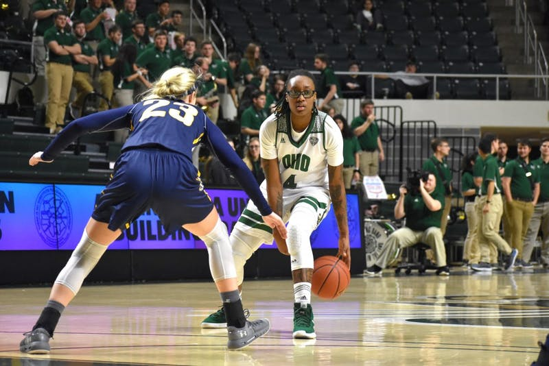 Ohio guard Erica Johnson (4) handles the ball against defensive pressure from Kent State's Ali Poole (23) during Ohio University's against Kent State on Wednesday.