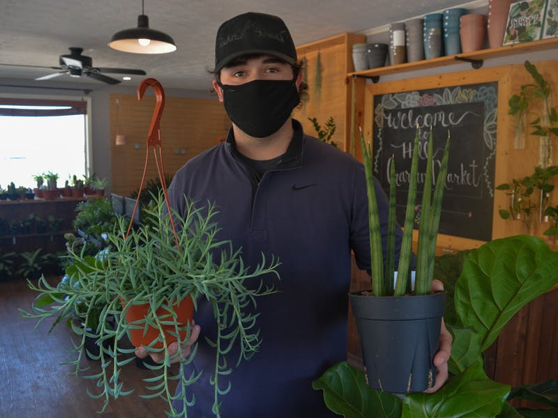 Hill Garden Market employee Connor Martin holds two of his favorite plants on April 13, 2021.