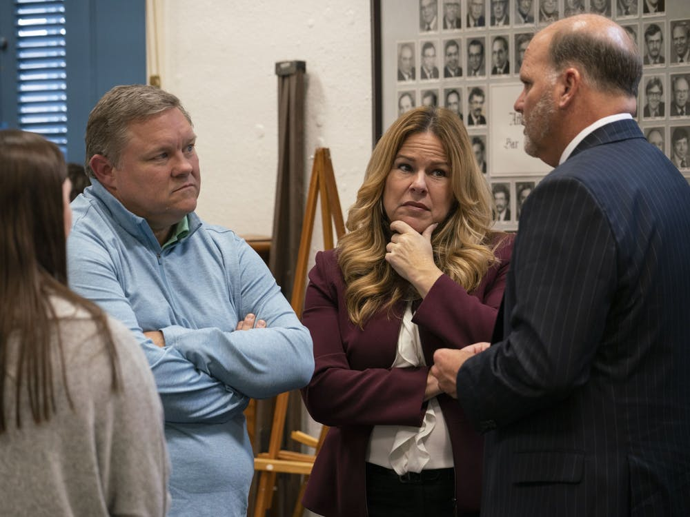 Kathleen, second from right, and Wade Wiant, second from left, discuss the case with their laywer Rex Elliot while waiting for the trial in the Athens Courthouse on November 21, 2019.