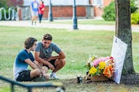 Two students kneel beside a memorial, on Monday, Sept. 9, 2019, in honor of a student who died at Ohio University.