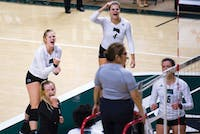 Carley Remmers (left) and Sara Januszewski cheers with the team after a point during Ohio's game against Miami on September 29, 2017 (Blake Nissen | File)