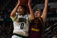 Ohio guard Jason Preston (No. 0) leaps to pass the ball as Central Michigan's forward David DiLeo (No. 14) attempts to block Preston in a match held at the Convo on Tuesday, Feb. 18, 2020 that would lead the Bobcats to victory with a winning score of 77 - 69.