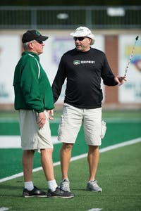 Defensive coordinator Jimmy Burrow, left, and offensive coordinator Tim Albin, right, run a drill during practice at Peden Stadium on Oct. 4, 2016. (FILE)