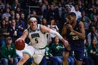 Ohio forward Ben Vander Plas (No. 5) dribbles past Akron's forward Xeyrius Williams (No. 20) in a Mid-American Conference match held at the Convo on Saturday, Jan. 25, 2020. The Bobcats will falter in the end against Akron with a close final score of 88-86.