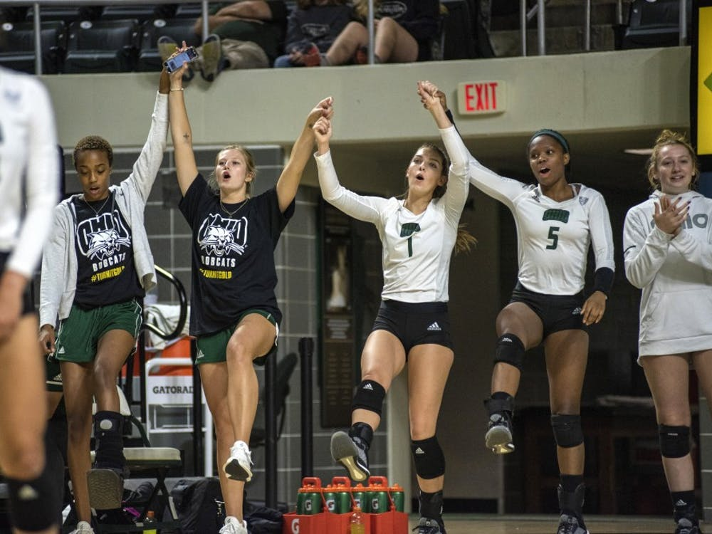 Ohio University women's volleyball team celebrating on the bench during games. They can be seen dancing, doing pushups and singing along to the songs playing between points.