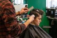 Maya Maynard recieves a haircut from barber Isaiah Dupler at The Chop Shop in Athens, Ohio, on February 19, 2019.