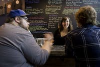 Bartender Ali Rutowski laughs as she takes an order from Elliot John-Conry, left, and Phil Ortman at Little Fish Brewing Company on Sept. 23. (FILE)