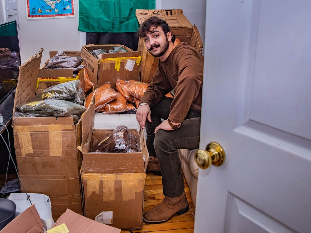 Ohio University student Dante Catanzarite, founder and owner of the Inferno & Co. clothing brand, holds an entire room full of the products that will be on the market soon for the winter season in his Mill Street home on Wednesday, Oct. 21, 2020.