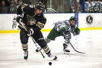 Ohio forward Tyler Harkins (22) chases a defenseman from Lindenwood during the second period of the Ohio hockey game against Lindenwood on Friday.