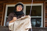 Talcon Quinn uses a cable wire to soften hide while demonstrating how to turn animal skin into leather during her hide tanning class at Solid Ground Farm on Sunday, Nov. 25.