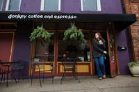 A customer exits Donkey Coffee, 17 1/2 W. Washington St., with a cup of coffee in hand. (FILE)