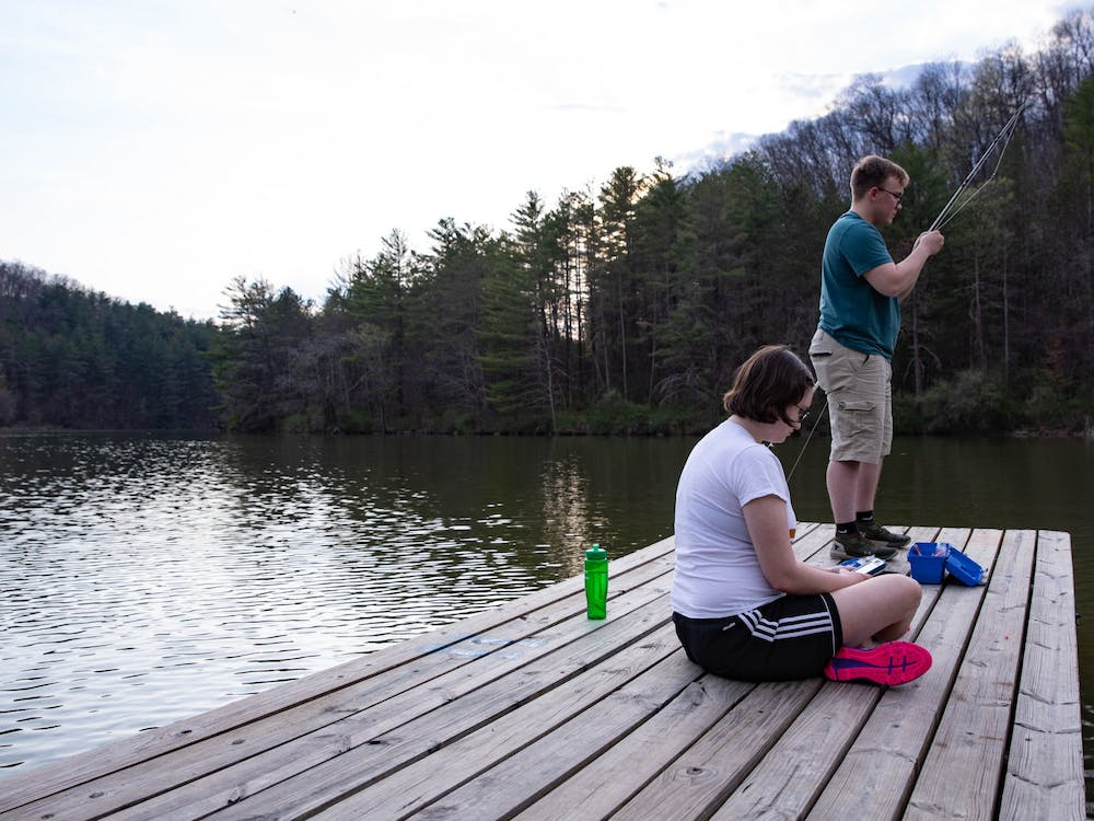Isabella Milstead sits patiently next to Sam Green as he ties fishing line to his pole on a dock at Dow Lake in Strouds Run State Park while soaking in the early spring warmth on Wednesday, April 7, 2021.