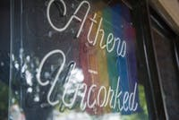 A rainbow flag hangs in the window of Athens Uncorked, a wine bar on Station Street, on Sept. 17. (FILE)