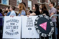 Christine Adams, left, and Susanna Hempstead, center, listen to a speaker during a rally outside of Ellis Hall on Feb. 24, 2017. The rally was held in response to the university's treatment of the sexual harassment allegations against English professor Andrew Escobedo. (FILE)