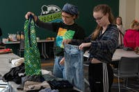 Chloe Jarrett (left) and Maggie Bennink (right) check out pants at the clothing swap on Sunday, Nov. 17 2019.