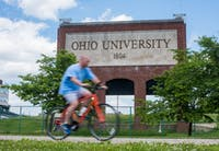 A man rides his bike on the Hockhocking Adena Bikeway, that passes in front of a Ohio University sign.